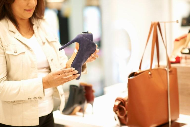 Consumidora olha calçados em loja de Dubai