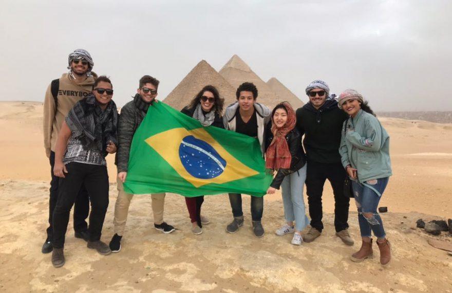Participantes de intercâmbio da Aiesec com as pirâmides egípcias ao fundo