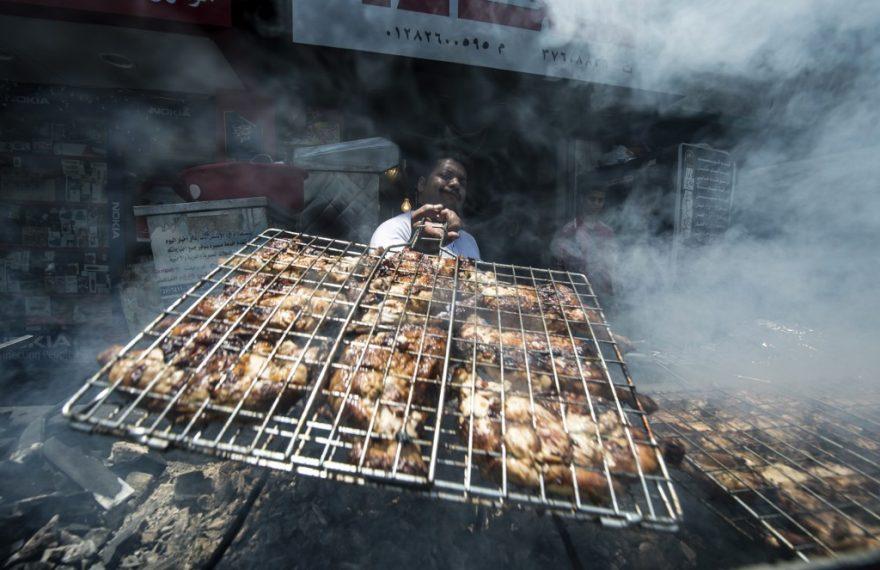 Cozinheiro assa frangos na brasa em restaurante do Cairo, Egito